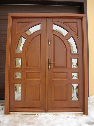 drzwi dwuskrzydłowe z drewna, szerokie skrzydła z przeszkleniami tworzącymi razem łuk, szyba reflex, zdjęcie wykonane przed osadzeniem drzwi, klamka stare złoto