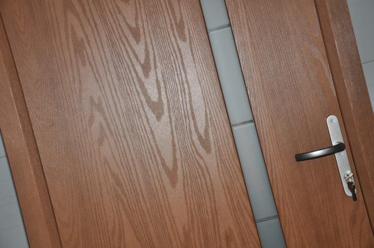 powierzchnia drewnopodobna w kolorze orzech na skrzydle i ościeznicy w drzwiach kompozytowych