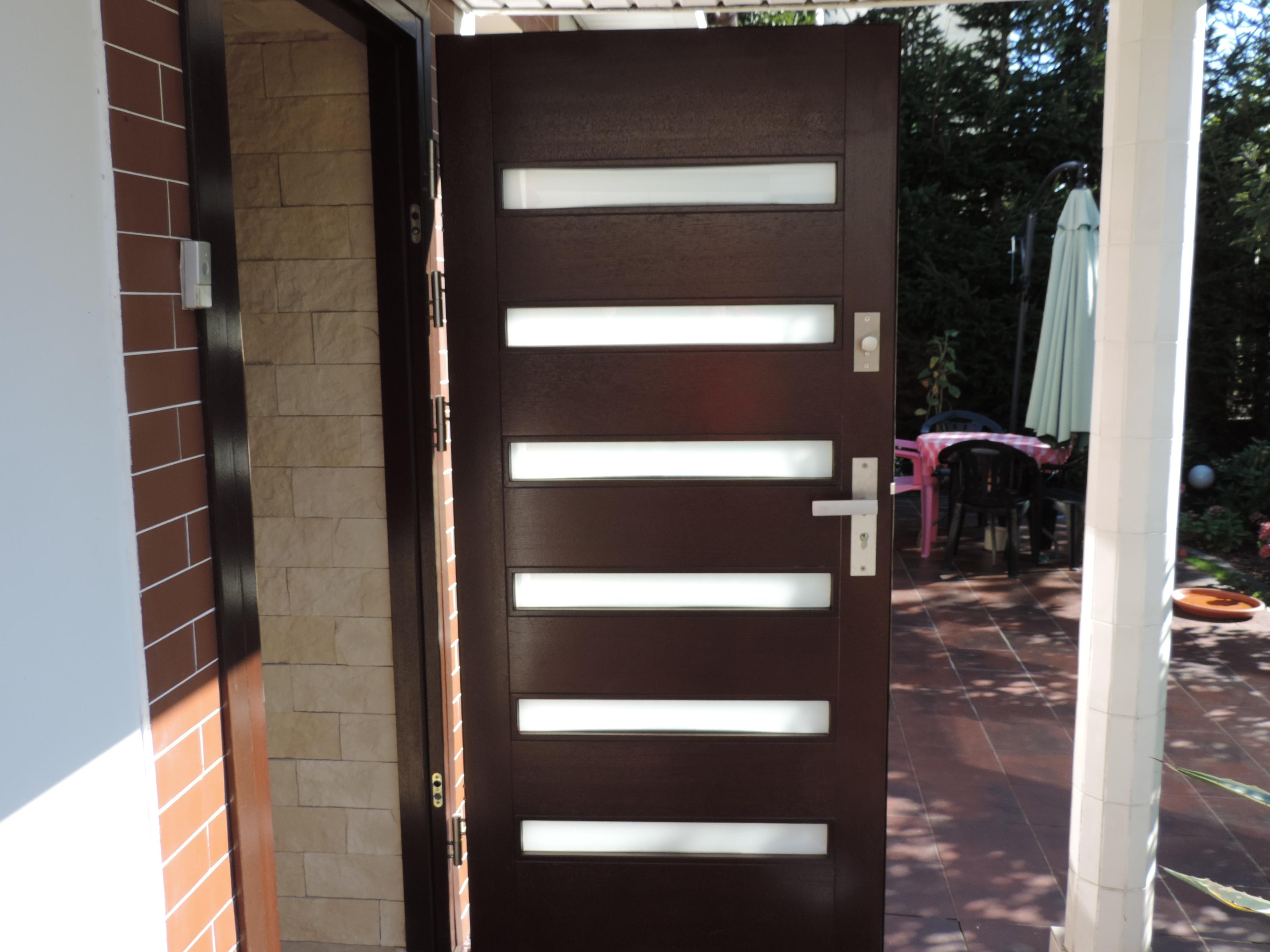wejściowe drzwi do domu z drewna z poziomymi przeszkleniami